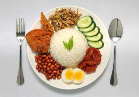 Nasi Lemak est un plat de riz imprégné de crème de noix de coco et chargé de poissons frits ou d'ailes de poulet. Banque d'images - 78793708
