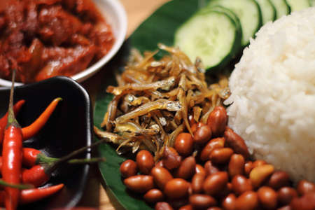 Nasi lemak is served with a hot spicy sauce, cucumber slices, small fried anchovies, roasted peanuts, and hard-boiled or fried egg.
