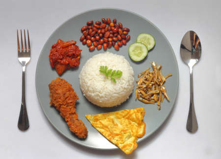 Nasi Lemak is a rice dish infused with coconut cream and laden with deep-fried fish or chicken wings.