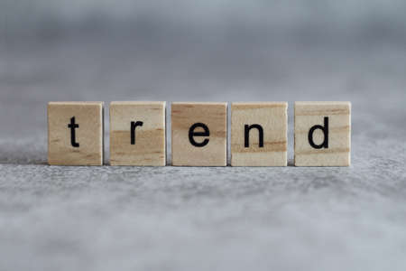 Trend word written on wood cube with gray background.