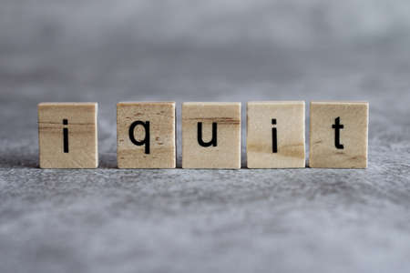 I quit word written on wood cube with gray background.