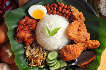 Nasi lemak is a dish that comprises rice made fragrant with coconut cream and pandan leaves.  Фото со стока