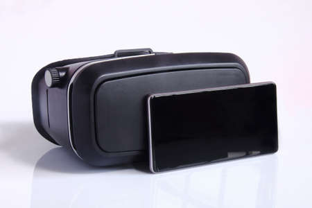 virtual reality glasses and smartphone isolated on white background. Virtual reality is a computer-generated scenario that simulates a realistic experience. Imagens