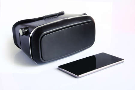 virtual reality glasses and smartphone isolated on white background. Virtual reality is a computer-generated scenario that simulates a realistic experience. Banco de Imagens