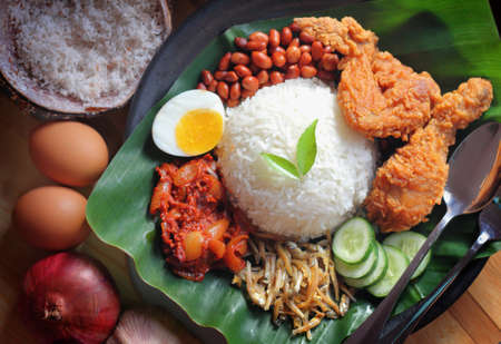 Nasi lemak is a dish that comprises rice made fragrant with coconut cream and pandan leaves. Stock Photo