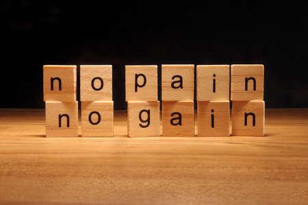 No pain no gain wooden blocks. Suffering is necessary in order to achieve something. Standard-Bild