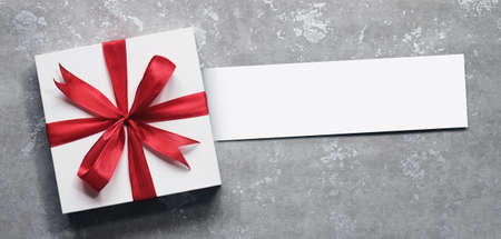 Top view of giftbox with greeting card on simple background. Wishing you wonderful memories during this joyous season.