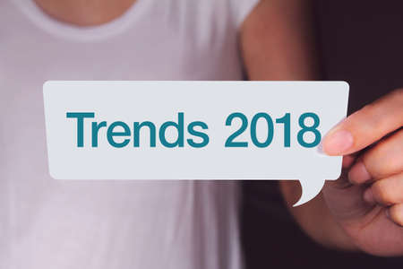 Trends 2018 wording on white talk bubble with hand.