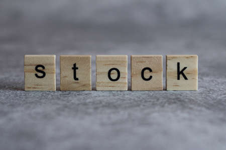 Stock word written on wood cube with gray background.