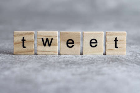 Tweet word written on wood cube with gray background.