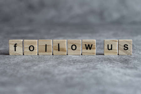 Follow us word written on wood cube with gray background.