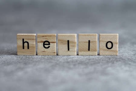 Hello word written on wood cube with gray background.