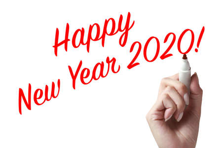 Hand holding a pen and writing happy new year 2020