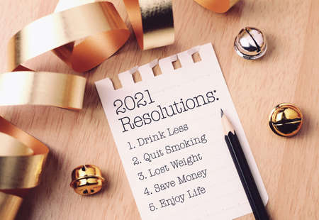 Resolutions 2021 with beautiful decoration. Discover how setting goals can bring more happiness in your life. Banco de Imagens