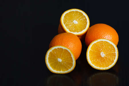 Halved and whole oranges over black background, side view. Space for text.