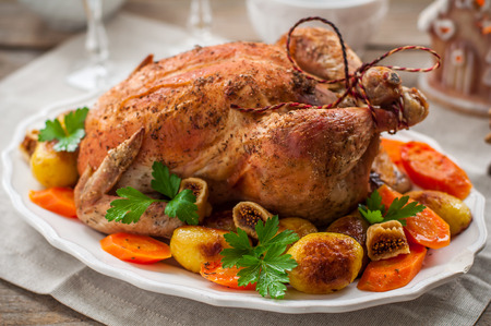 Christmas Stuffed  Chicken Served with Potatoes, Carrots and Figs on a Wooden Table