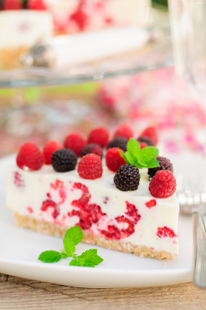 black raspberries: A Piece of No-bake Fresh Raspberry Cheesecake with Red and Black Raspberries and Melissa, Summer Cake, copy space for your text, close up Stock Photo