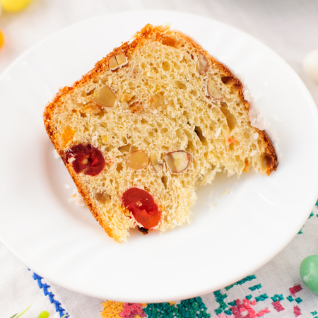 russian easter: A Slice of Kulitch (Kulich), Russian Easter Sweet Bread on Festive Embroidered Table Cloth, close up, square, copy space for your text