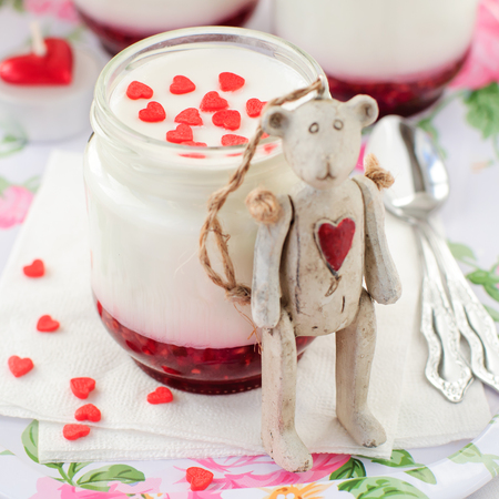 bear berry: A Jar of Natural Yoghurt with Raspberry Jam Decorated with Sugar Hearts and Antique Teddy Bear Toy with a Red Heart on His Chest Leaning over It, selective focus on sugar hearts, copy space for your text