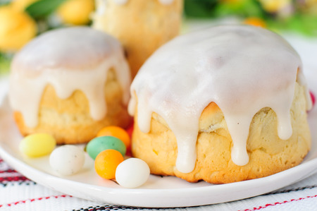 russian easter: Kulitch (Kulich), Russian Easter Bread Topped with Sugar Icing Decorated with Easter Eggs Candies, close up, copy space for your text