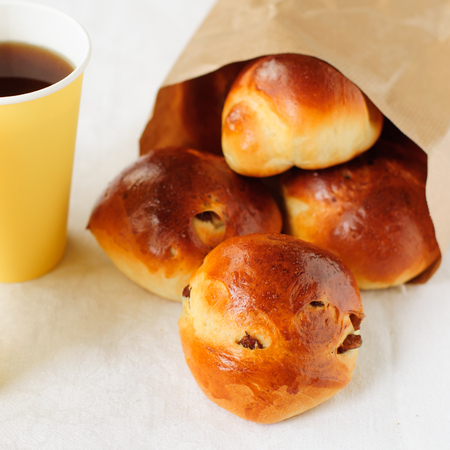 sultana: Sultana Buns in a Paper Bag with a Cup of Coffee Stock Photo