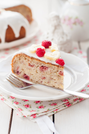 icing sugar: A Piece of Banana Cake with Sugar Glaze Topped with Raspberries and Banana Slices