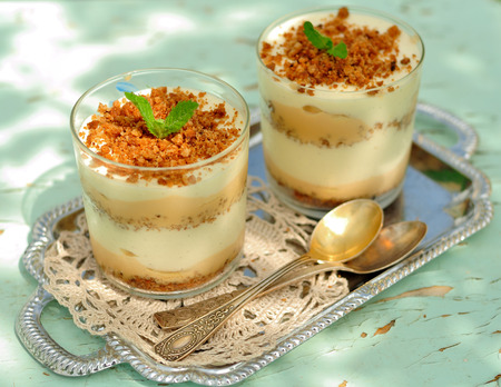 Layered Dessert in Glasses, crumbled biscuit, caramel sauce, vanilla custard and bananas