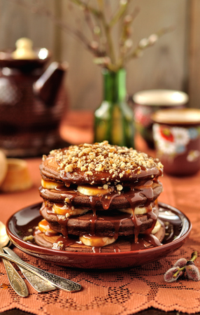 walnut cake: A stack of chocolate pancakes with bananas, caramel sauce and walnuts
