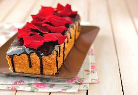 special occasions: Cake loaf with chocolate glaze and rose petals, good for birthday, St. Valentines day and other special occasions; copy space for your text.