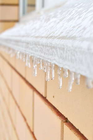 ledge: Icicles hanging from a ledge, frozen in winter or eavesdripping in spring