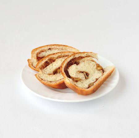 cinnamon swirl: Cinnamon and walnut swirl bread slices over white background Stock Photo
