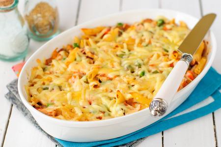 白いセラミック皿で焼くマカロニ、かぼちゃ、鶏とチーズのパスタ