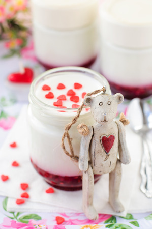 bear berry: Antique Teddy Bear Toy with a Red Heart on His Chest Leaning over a Jar of Natural Yoghurt with Raspberry Jam Decorated with Sugar Hearts, selective focus on toys head, copy space for your text Stock Photo