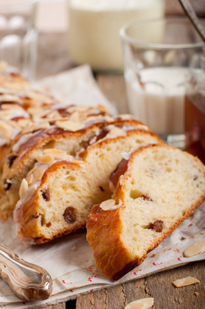 flaked: Sliced Braided Sweet Bread with Raisins and Orange Zest Topped with Sugar Glaze and Flaked Almonds