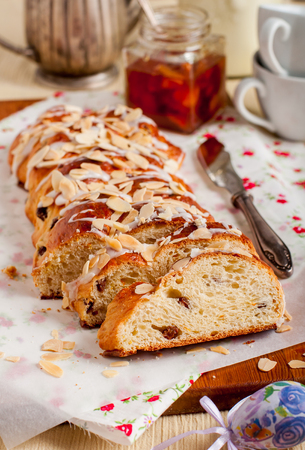 flaked: Sliced Easter Braided Sweet Bread with Raisins and Orange Zest Topped with Sugar Glaze and Flaked Almonds