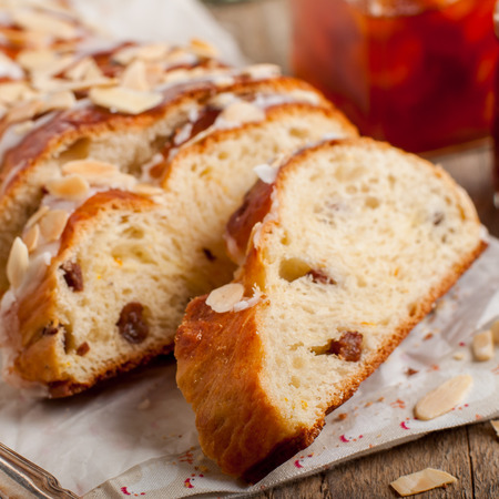 jewish cuisine: Sliced Braided Sweet Bread with Raisins and Orange Zest Topped with Sugar Glaze and Flaked Almonds