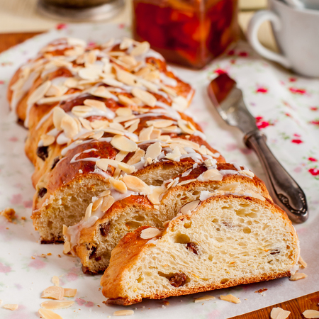 flaked: Sliced Braided Sweet Bread with Raisins and Orange Zest Topped with Sugar Glaze and Flaked Almonds, square