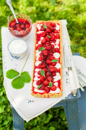 Orange Curd Tart with Vanilla Roasted Strawberries on a Step Stool, copy space for your text
