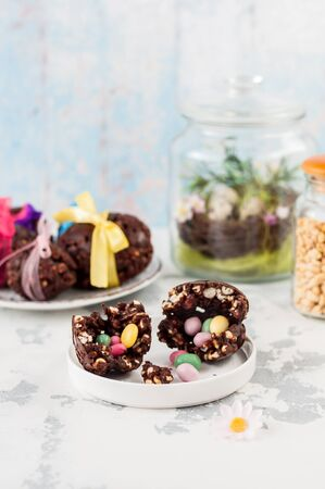 Cracked Easter Chocolate and Puffed Wheat Egg with Hidden Surprise Candies, copy space for your text Stock Photo