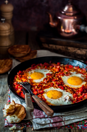 Shakshouka, Middle East and North Africa Dish of Poached Eggs in a Sauce of Tomatoes, Chili Peppers and Spices, copy space for your text