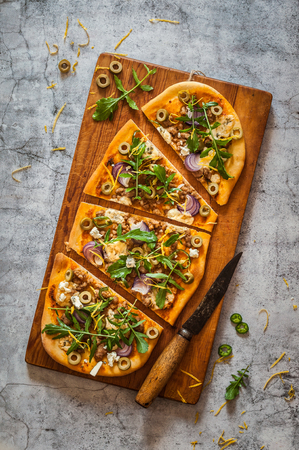table top: Sliced Free Shaped Pork, Blue Cheese, Green Chili and Red Onion Pizza Stock Photo
