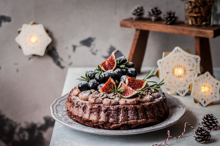 Chocolate Christmas Cake Decorated with Figs, Grapes, Walnuts and Rosemary Stock Photo