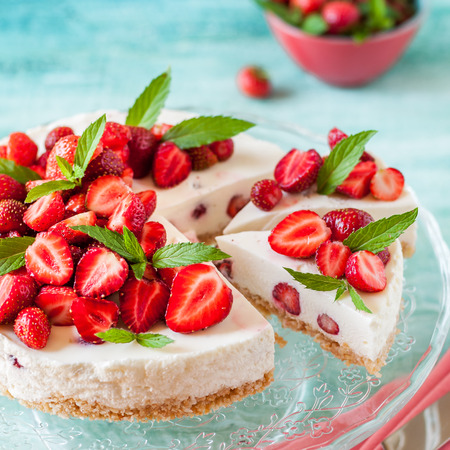 Sliced No Bake Strawberry Cheesecake Decorated with Fresh Berries and Mint, square