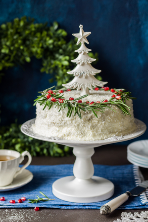 retro christmas: Cristmas Coconut Cake Decorated with Rosemary, Pomegranate and a Toy Tree Stock Photo