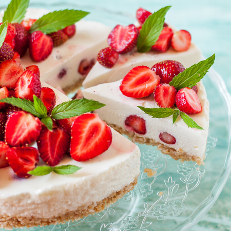 Sliced No Bake Strawberry Cheesecake Decorated with Fresh Berries and Mint, close up, square