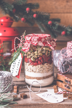 Christmas Cookie Mix in a Jar, Layered Flour, Brown and Caster Sugar, Oats, Dried Cherries and Pistachios, copy space for your text