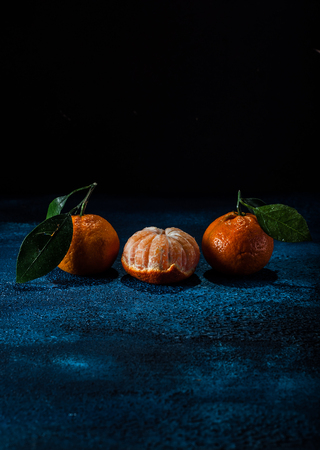 A Group of Three Tangerines on Dark Blue Concrete Background, copy space for your text
