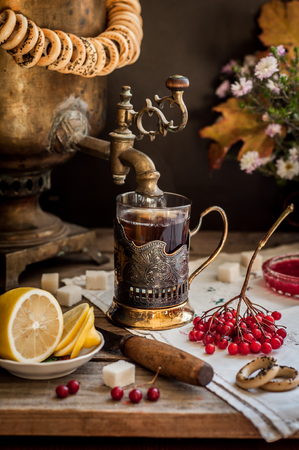 Russian Tea from Samovar, A Glass in Glass Holder, Black Tea with Viburnum Berries, copy space for your text Stock Photo