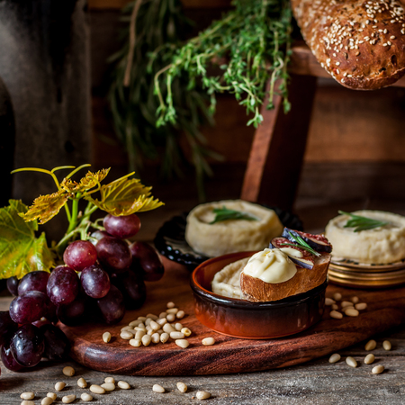 Soft Spreadable French Stinky Cheese on a Slice of Bread with Fruit and Pine Nuts, square Archivio Fotografico - 116465573