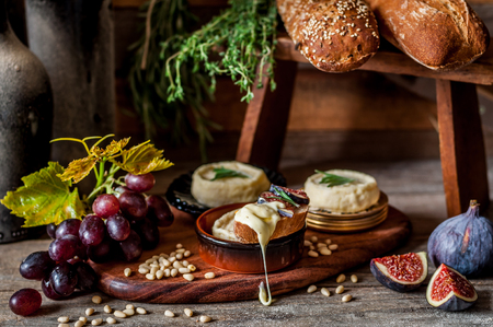 Soft Spreadable French Stinky Cheese on a Slice of Bread with Fruit and Pine Nuts Archivio Fotografico - 116465571